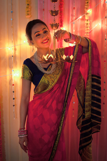 Beautiful Indian woman smiling while holding hanging diya lamps - Diwali Festival