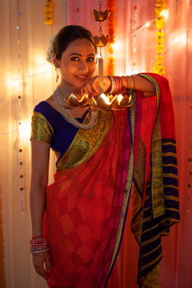 Indian woman in traditional dress posing on  the camera on Diwali - Indian festoval
