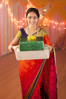 Portrait of a smiling pretty female holding a stack of gift boxes - Diwali festival celebration