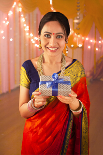 Pretty Indian woman holding a gift box and looking at the camera - Diwali Festival