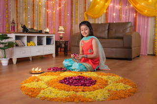 Cute Indian girl making beautiful rangoli using flowers petals - Festival celebration