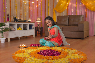 Beautiful Indian girl feeling happy, making flower (petals) rangoli on Diwali Festival