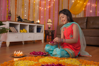 Portrait of Indian girl with smiling face making flower petals rangoli in her house/apartment for Diwali