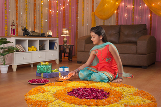 Stock Image of lovely Indian girl making flower rangoli with Diya