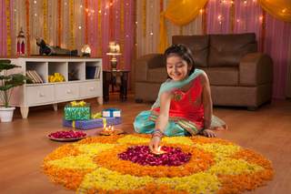 A cute girl making rangoli with flower petals and diya - Festival Image