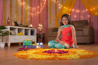 Stock Image of a cute and smiling Indian girl sitting near flower rangoli