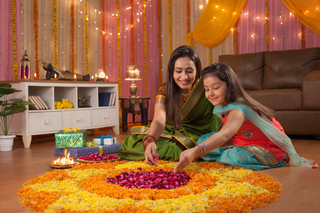 Beautiful mother and daughter making rangoli on diwali festival - Colorful background