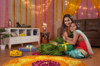 Beautiful little girl sitting with her mother near rangoli and enjoying Diwali preparation - Festival Concept