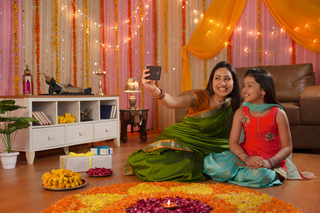 Image of a beautiful little girl posing with her mother for a selfie/self photograph - Festival celebration