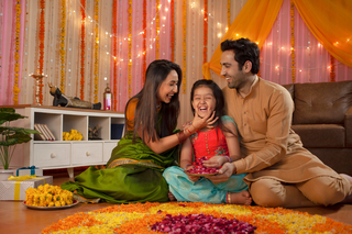 Stock image of a happy family - mother loving her daughter. Making rangoli and enjoying Diwali