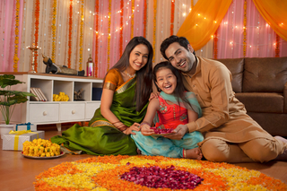Happy Indian family posing towards camera while making flower rangoli for Diwali festival