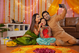 Smart Indian family taking a selfie with smartphone near Diwali rangoli: Festival and technology concept