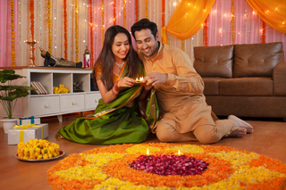 Smart Indian Couple in traditional dress arranging Diyas around flower Rangoli on Diwali Festival Night
