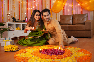 Diwali Celebration - Indian wife holding tray / thali of diyas and husband arranging diyas to decorate home