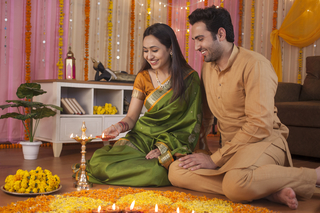 Young couple decorating their house on Diwali and lighting Diyas together - Hindu festival custom