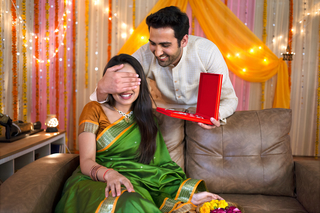 Romantic Husband surprising his wife with a gift by closing her eyes: birthday / anniversary / festival / diwali