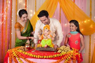 Cheerful Indian family welcoming Lord Ganesha idol on Ganesh festival / Ganesh Chaturthi