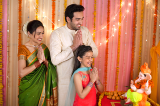 A happy Indian family seeking blessings from Lord Ganesha on Ganesh Chaturthi - Praying with folded hands