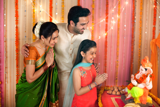 A happy Indian family in traditional dress performing puja / pooja at Ganesh festival: Hindu religion