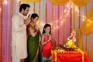 Portrait of an Indian family doing puja / pooja at Ganesh Chaturthi: Hindu customs religion