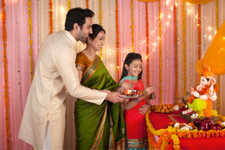 An Indian family dressed in traditional clothes performing aarti during Ganesh puja / pooja