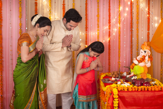 Spiritual Indian family with folded hands praying to Lord Ganesha idol - Festival
