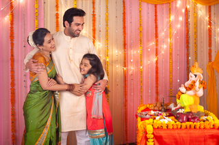 Happy nuclear family: father hugging his wife and daughter  -  Ganesh Chaturthi Celebration