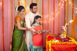 Traditional Indian family worshiping Lord Krishna on Krishna Janmashtami - Festival concept