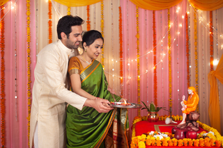 A happy newlywed Indian couple doing aarti together in the tradtional dress - Festival celebration