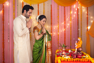 A smart Indian couple performing Sai pujan or puja on the occasion of Guru Purnima - Festival Celebration