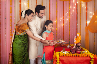 Indian family performing Sai Baba pooja at home