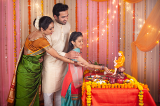 Indian family - mother, father and daughter doing prayer - Sai Baba