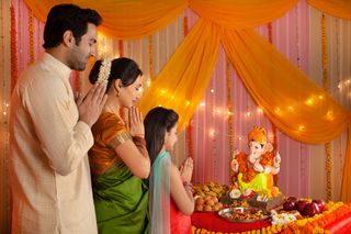 Indian nuclear family in traditional dress celebrating Ganesh chaturthi