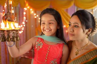 Indian mother and daughter lighting diyas on Diwali festival