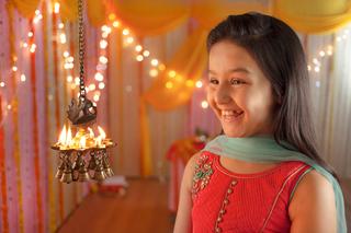 Cute little girl lighting up diyas for festival - diwali