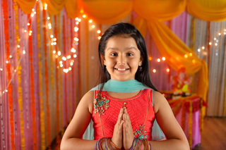 Cute little Indian girl greeting (namaste) on festival having lord Ganesha at the background