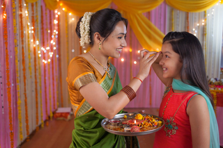 Indian mother and daughter celebrating festival together and putting tilak on her forehead