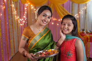 Indian mother and daughter celebrating festival and doing pooja
