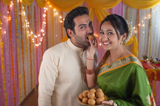 Indian wife and husband celebrating festival together and eating sweets - ladoo / laddu