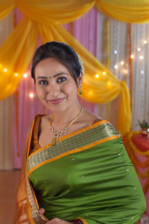 Beautiful Indian lady draped in traditional saree with festive background