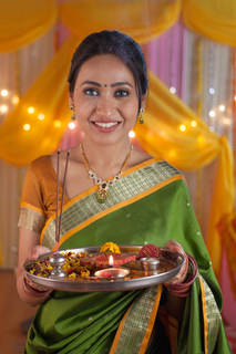 Young traditional woman holding pooja thali - wearing saree during festival time
