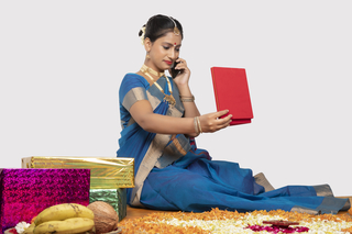 Young smiling south Indian woman in elegant saree is talking on the phone while looking at her gift - white background