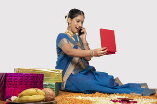 Surprised south Indian woman is sitting and looking at her festival gift while talking on the phone - white background