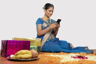 Portrait of a south Indian lady sitting in saree and looking at her mobile phone - home decoration, festival concept