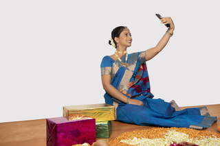 Young south Indian woman is taking selfie with a smartphone - Gifts, Rangoli with white background