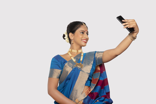 Beautiful south Indian woman taking a selfie or self-portrait with mobile - standing with white background