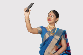 Smiling south Indian woman taking her self-portrait/selfie with her mobile/smartphone - white background