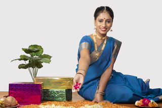 Image of a beautiful south Indian woman making flower rangoli on the festival - white background