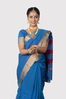 Young south Indian woman in traditional outfit holding a diya in her hands - standing and looking towards the camera with white background