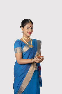 Portrait of a smiling south Indian woman standing with a white background holding a diya in her hands